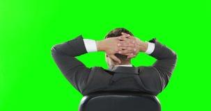 Vista posterior del hombre de negocios que se relaja en su silla almacen de metraje de vídeo