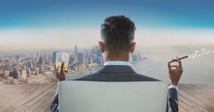 Vista posterior del hombre de negocios que se sienta en silla con el vidrio del alcohol y del cigarro que fuma mientras que mira  Imagenes de archivo
