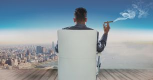Vista posterior del hombre de negocios que se sienta en silla y que mira el mar mientras que fuma el cigarro imagenes de archivo