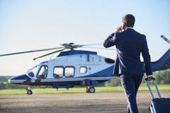 Vista posterior del hombre de negocios Walking Towards Helicopter mientras que Talki imagenes de archivo