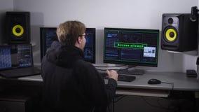 Vista posterior del hombre en un pirata informático que finalmente rompió el programa y accedió a los datos confidenciales Tenga  almacen de metraje de vídeo