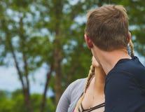 Vista posterior del hombre joven que besa a su novia Fotos de archivo libres de regalías