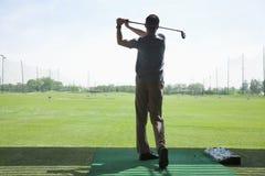 Vista posterior del hombre joven que golpea las pelotas de golf en el campo de golf, brazos aumentados Imagen de archivo libre de regalías
