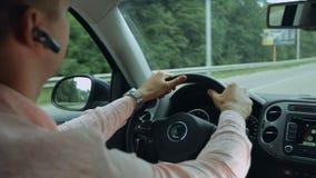 Vista posterior del hombre que conduce el coche en la carretera almacen de metraje de vídeo