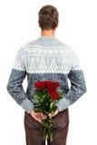 Vista posterior del hombre que oculta rosas rojas Imagenes de archivo