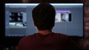 Vista posterior del hombre que trabaja en el ordenador de la pantalla ancha metrajes