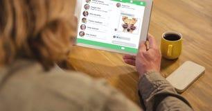 Vista posterior del hombre que usa la tableta digital con el medios interfaz social en la pantalla Imagen de archivo