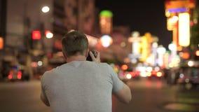 Vista posterior del hombre turístico joven que fotografía las calles de Chinatown en la noche metrajes