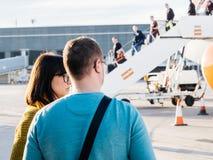 Vista posterior del hombre y de la mujer que miran el avión o de EasyJet Airbus foto de archivo