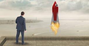 Vista posterior del lanzamiento del cohete del hombre de negocios que hace una pausa mientras que mira el mar Imagen de archivo