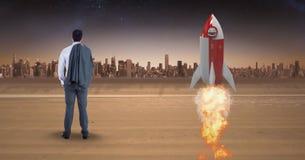 Vista posterior del lanzamiento del cohete del hombre de negocios que hace una pausa mientras que mira la ciudad Fotos de archivo libres de regalías