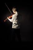 Vista posterior del muchacho con el violín en fondo negro Foto de archivo