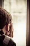 Vista posterior del muchacho que mira hacia fuera la ventana Imagen de archivo libre de regalías
