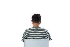 Vista posterior del muchacho que se sienta en silla Fotografía de archivo