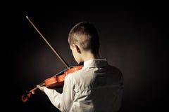 Vista posterior del niño que toca el violín en sitio oscurecido Fotografía de archivo libre de regalías