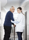 Vista posterior del paciente feliz del doctor Walking With Senior imagen de archivo