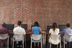 Vista posterior del personal en los escritorios usando los ordenadores en oficina ocupada fotografía de archivo