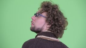 Vista posterior del primer del hombre joven con el pelo rizado que piensa y que espera almacen de video