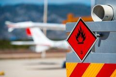 Vista posterior del servicio y del camión de reaprovisionamiento de combustible en un aeropuerto con un avión en el fondo borroso Imagenes de archivo