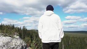 Vista posterior en el hombre que se coloca en el acantilado de la montaña metrajes
