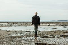 Vista posterior en el solo muchacho rubio que camina en la playa Fotos de archivo libres de regalías
