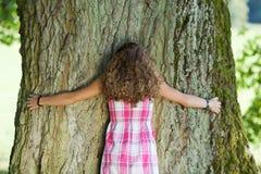 Vista posterior en la muchacha que abraza un árbol Imagen de archivo