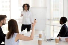 Vista posterior en la mujer que aumenta la mano que pide concepto de la pregunta imágenes de archivo libres de regalías