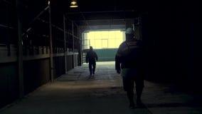 Vista posterior en la silueta de los trabajadores industriales que caminan en pasillo de la producción en la planta metalúrgica D almacen de video
