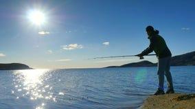 Vista posterior muy cercana al pescador de trabajo Sirva el control que empuja cebo y tiros él lejos en el mar Silueta del hombre almacen de metraje de vídeo