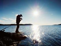 Vista posterior muy cercana al pescador de trabajo Sirva el control que empuja cebo y tiros él lejos en el mar imagen de archivo libre de regalías