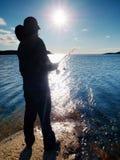 Vista posterior muy cercana al pescador de trabajo Sirva el control que empuja cebo y tiros él lejos en el mar fotografía de archivo