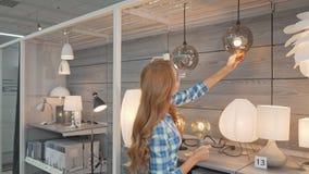 Vista posterior tirada de un cliente femenino que elige las lámparas en la tienda de muebles metrajes