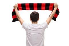 Vista posterior tirada del aficionado al fútbol adolescente que sostiene la bufanda Foto de archivo libre de regalías