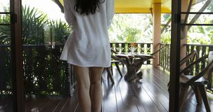 Vista posterior trasera de la mujer en puerta abierta de la camisa del hombre blanco y de la salida en la terraza, muchacha moren metrajes