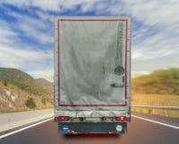 Vista posteriore del contenitore di trasporto del carico del camion di musica sulla strada maestra Immagini Stock