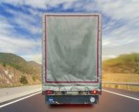 Vista posteriore del contenitore di trasporto del carico del camion sull'alta strada di modo Immagini Stock