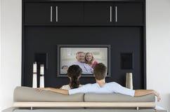 Vista posteriore del film di sorveglianza delle coppie sulla televisione in salone Fotografia Stock
