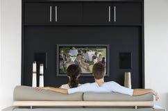 Vista posteriore del film di sorveglianza delle coppie sulla televisione in salone Immagini Stock