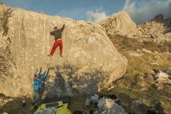 Vista posteriore del masso rampicante della roccia della gente nel tramonto immagini stock libere da diritti