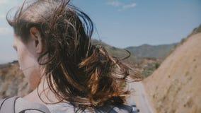 Vista posteriore del primo piano sparata di giovane donna turistica con capelli che volano in forte vento che gode della vista al stock footage
