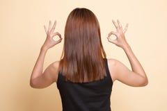 Vista posteriore del segno asiatico della mano di APPROVAZIONE del doppio di manifestazione della donna immagine stock libera da diritti