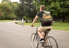 Vista posteriore della bici moderna di guida dell'uomo dei pantaloni a vita bassa nel parco Fotografia Stock Libera da Diritti