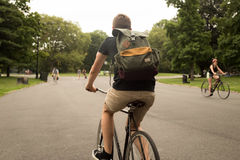 Vista posteriore della bici moderna di guida dell'uomo dei pantaloni a vita bassa nel parco Immagine Stock