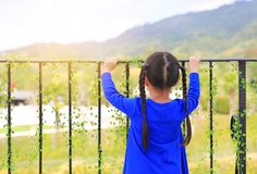 Vista posteriore della condizione della bambina alle barre del balcone e di osservare fuori alla natura la mattina fotografia stock