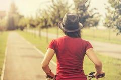 Vista posteriore della guida della giovane donna sulla bici Immagini Stock