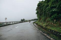 vista posteriore della motocicletta di guida della gente sulla strada della montagna in Hai Van Pass, Vietnam Immagine Stock Libera da Diritti