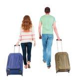 Vista posteriore delle coppie di camminata con la valigia Fotografie Stock Libere da Diritti