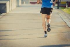 Vista posteriore delle gambe e delle scarpe di giovane funzionamento atletico dell'uomo nell'allenamento di forma fisica di estat Immagine Stock Libera da Diritti
