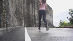 Vista posteriore di funzionamento della donna di forma fisica sulla strada La gente e concetto di sport stock footage