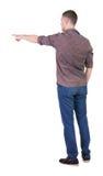 Vista posteriore di indicare i giovani in camicia e jeans Fotografie Stock